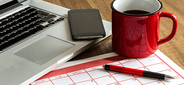 Laptop, calendar, pen, coffee cup, and cell phone on a table.