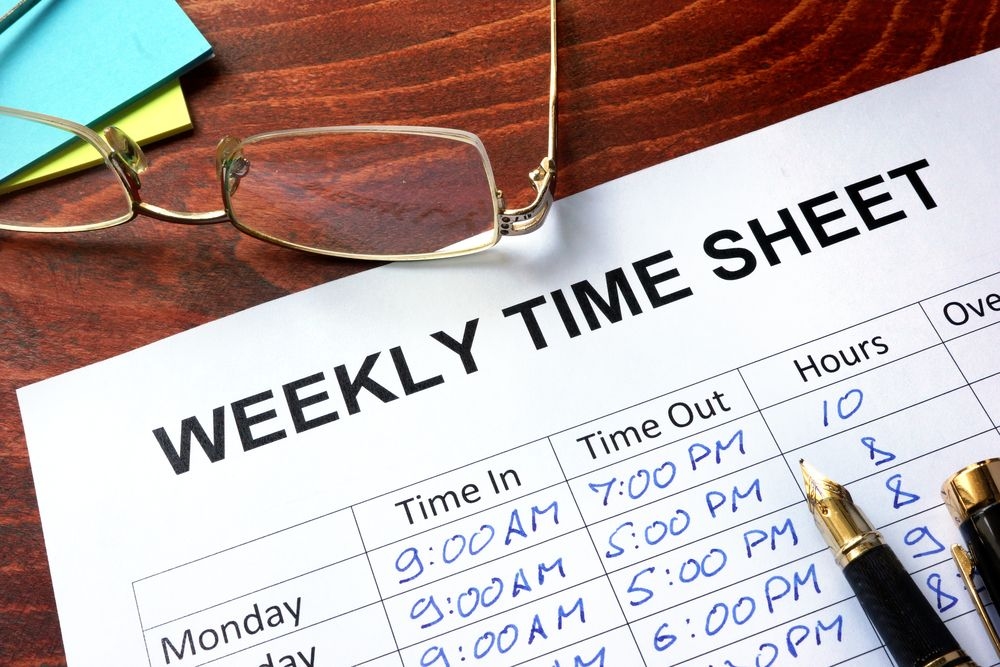 "Piece of paper on a table titled ""weekly time sheet"""