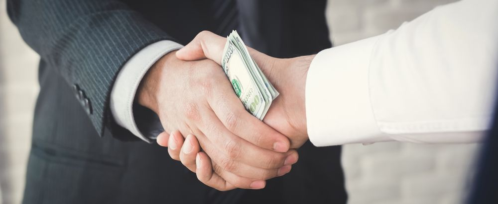 Two people exchanging money through a handshake